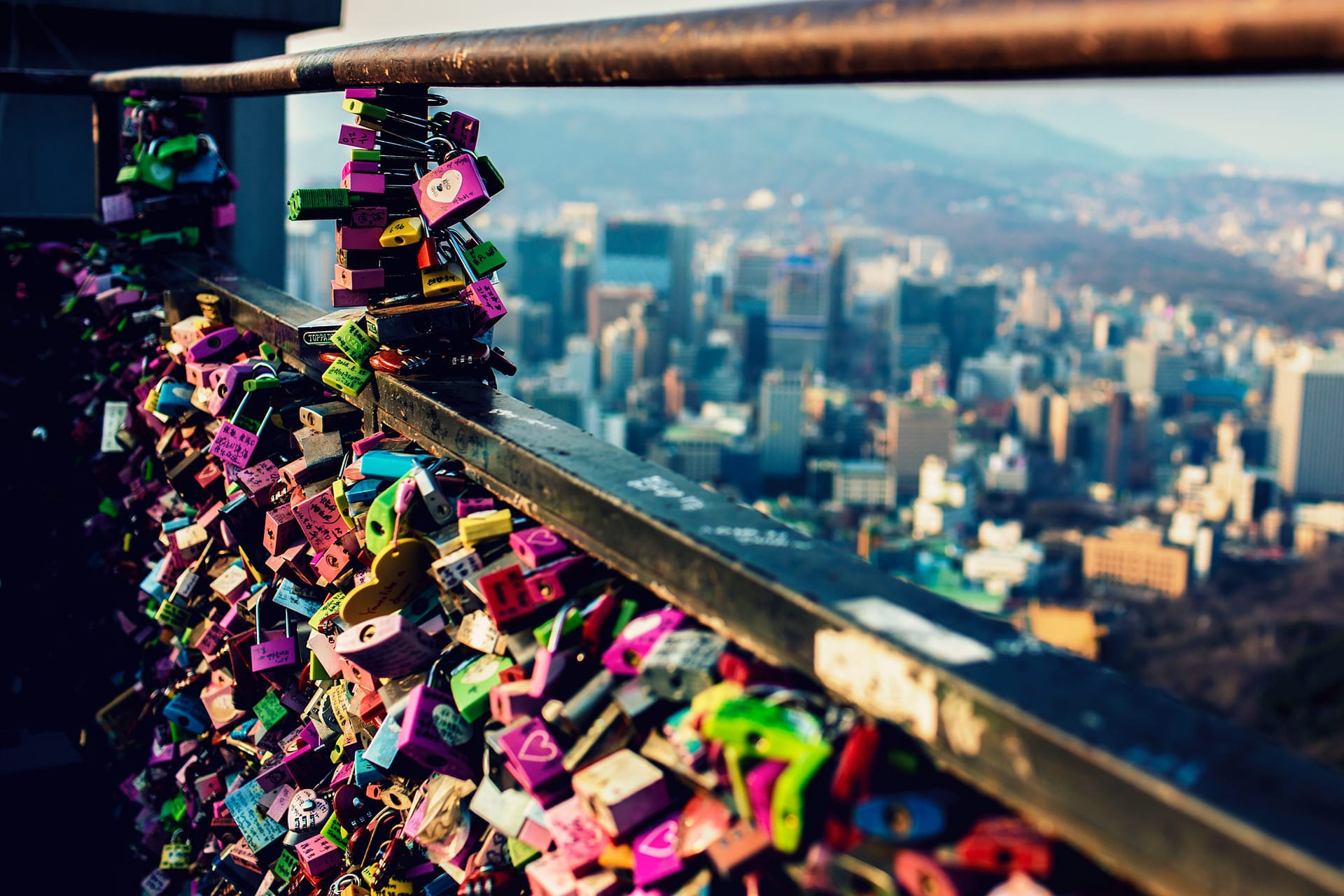 The popular Love Locks at N Seoul Tower with a view of the city of Seoul in the background