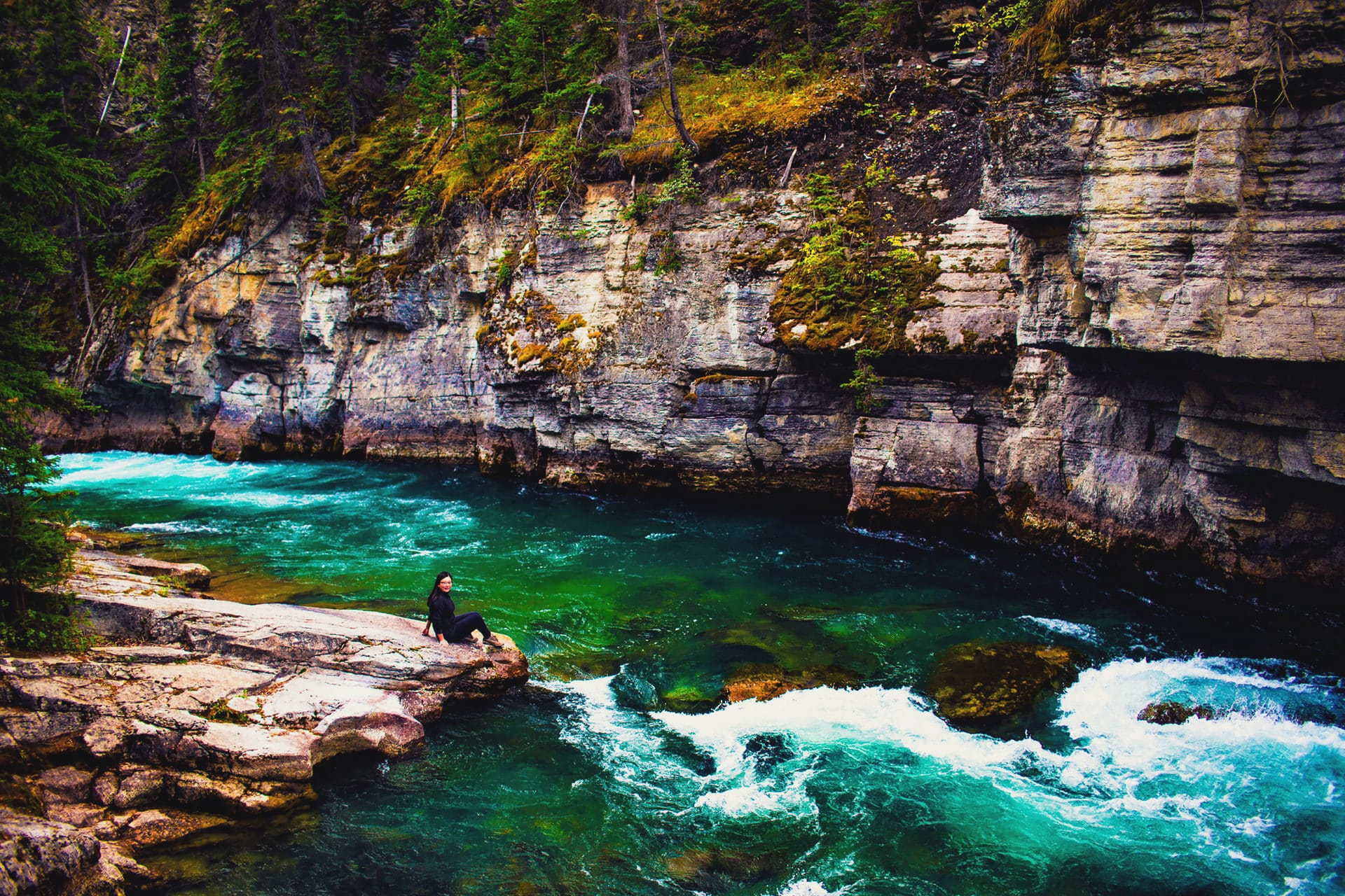 Girl sitting on rocks at the river edge at Maligne Canyon Hike in Jasper National Park Alberta Canada