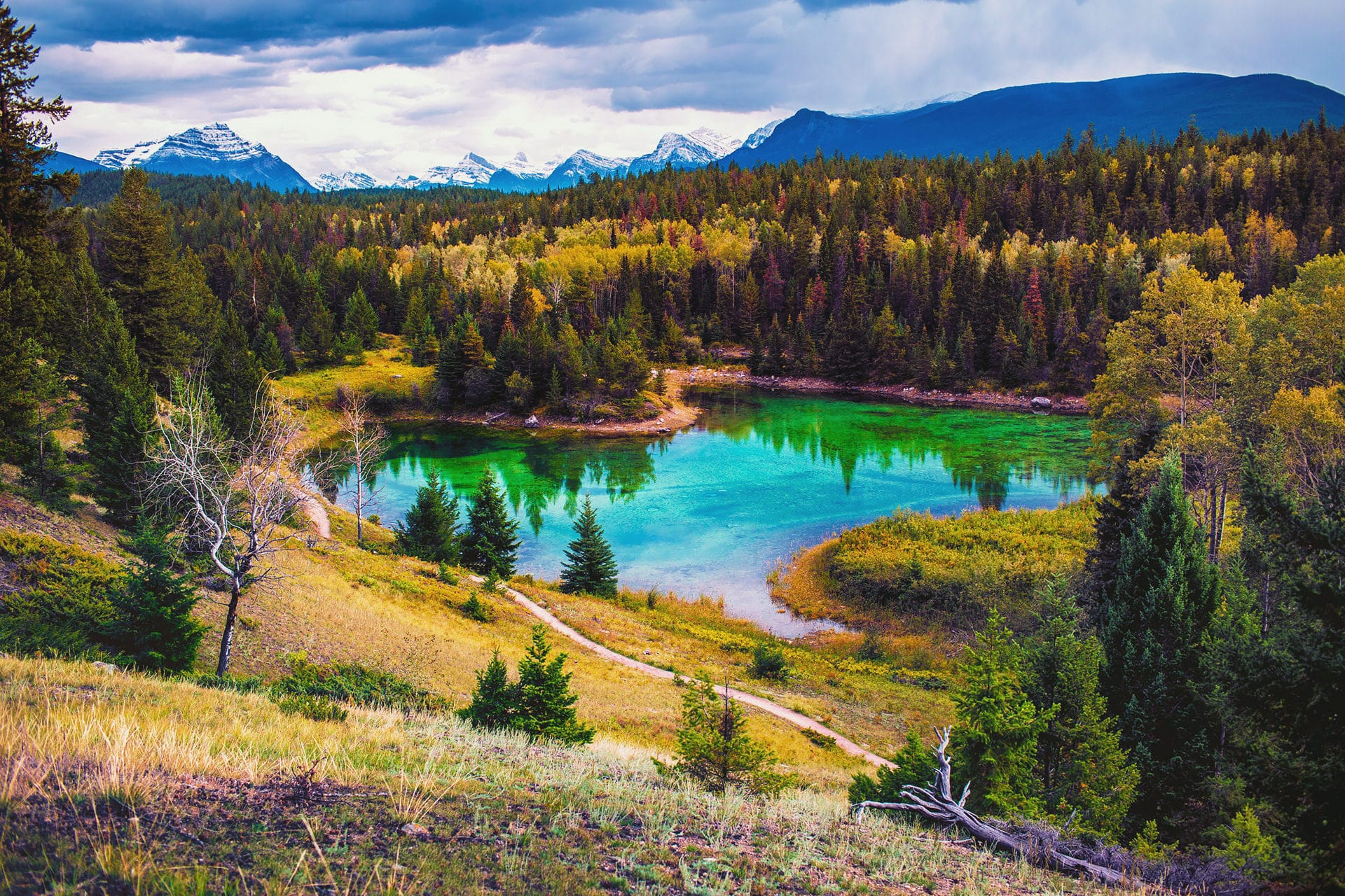 Turquoise lake surrounded by glacial capped mountains at valley of the five lakes in Jasper National Park