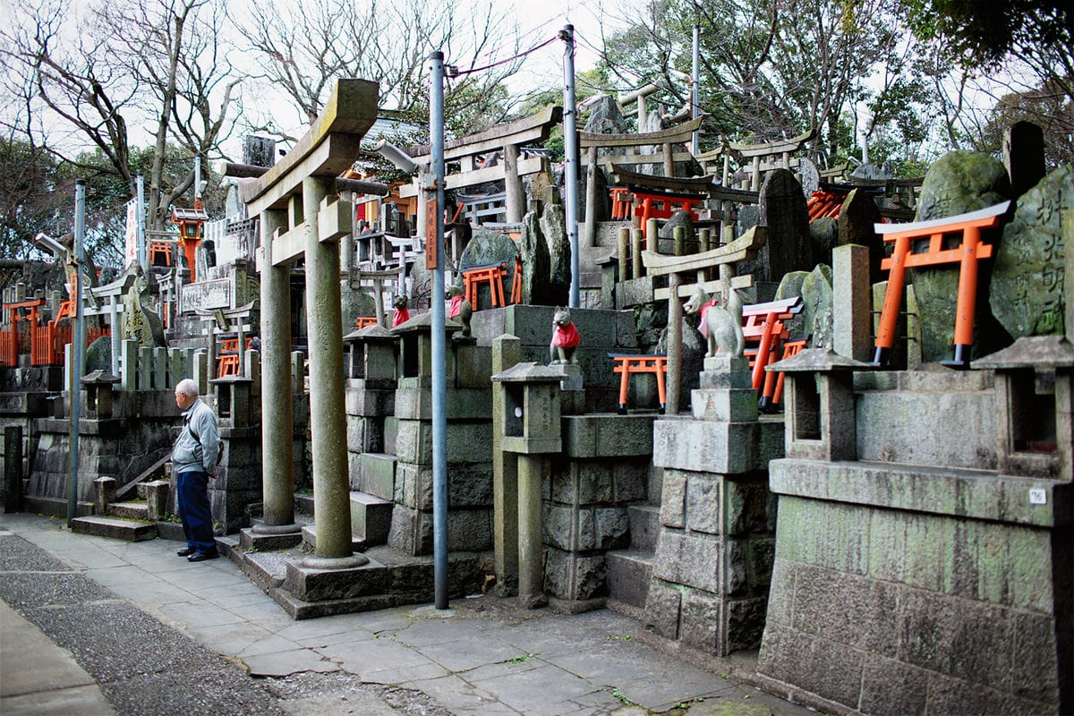 older gentleman standing in front of many tiny shrines at fushimi inari taisha shrine