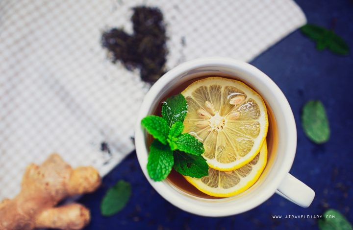ginger tea in a white mug with lemon slices and a sprig of mint for morning detox